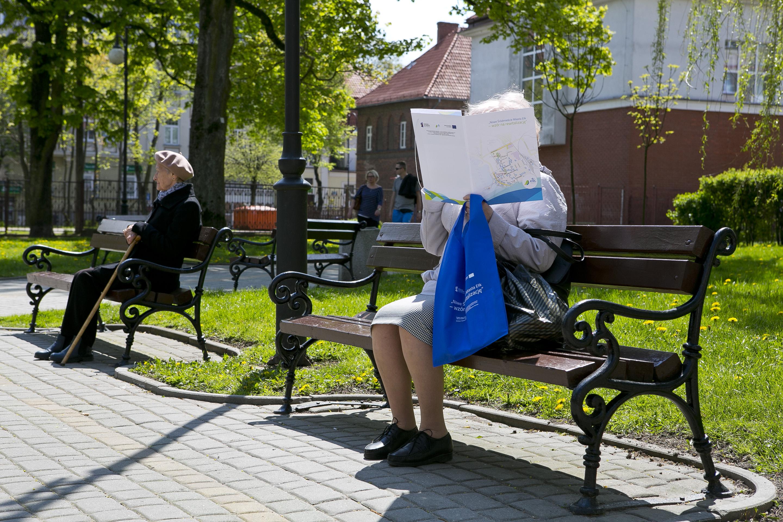 Osoby starsze siedzą na ławkach przy ul. Słowackiego. Czytają materiały na spotkanie konsultacyjne.