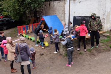 Na podwórku, grupa dzieci wraz z dorosłymi buduje plac zabaw.