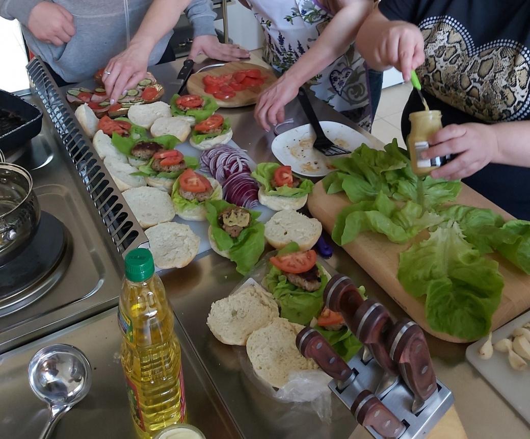 Zdjęcie przedstawia proces przygotowywania hamburgerów (produkty spożywcze).
